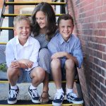 two boys sitting with their mom on the steps