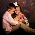 brother and sister holding sleeping sibling baby