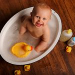 baby in bath smiling with rubber ducky
