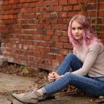 girl with pink hair posing in alley