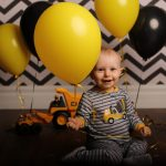 baby holding yellow and black balloons