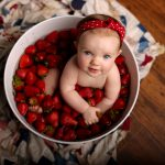 baby sitting in bath of strawberries