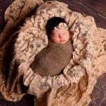 baby sleeping in tan fluff