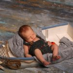 baby sleeping in toy boat