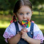little girl eating a rainbow sucker